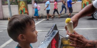 COLD TREAT. A young boy visibly can't contain his excitement as he waits for a vendor to hand him his scoop of ice cream he bought along San Pedro Street in Davao City on Saturday. LEAN DAVAL JR.