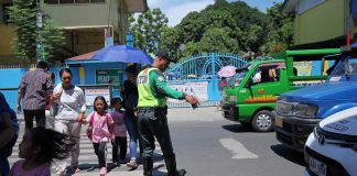 HELP AT HAND. A City Transport and Traffic Management Office (CTTMO) traffic enforcer assists pedestrians who are mostly young students cross the street along Magallanes Street in Davao City on Thursday.LEANDAVAL JR.