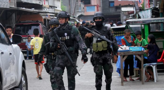 SECURITY CHECK. Members of the Davao City Police Office's Special Weapons and Tactics unit, together with other police personnel and Task Force Davao, conduct a surprise a 'saturation operation' in Mini-forest, Quezon Blvd., Davao City on Saturday morning. LEAN DAVAL JR.
