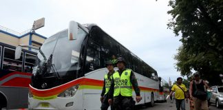 READY TO ASSIST. Police officers from the Davao City Police Office (DCPO) walk by the passenger buses commissioned by the city government of Davao are stationed along San Pedro Street in Davao City on Thursday to accommodate stranded commuters as Transmission- Piston Southern Mindanao staged a transport strike. Hundreds of police officers were deployed by DCPO to secure passenger buses and the riding public LEAN DAVAL JR.