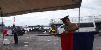 Philippine Navy personnel carefully fold back for safekeeping the flags of the Philippines and Indonesia after an arrival ceremony for the visiting Indonesian navy at Sasa Port in Davao City on Monday. LEAN DAVAL
