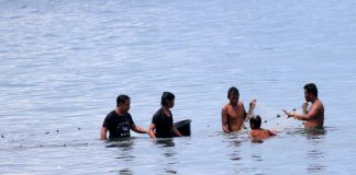 TWO AT A TIME. A group of men tries to catch fish for their lunch while swimming at the beachfront at Sta. Ana Port in Davao City on Tuesday. LEAN DAVAL JR.