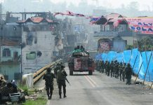 Damaged buildings loom in the background as Philippine Marines backed by a V300 armored vehicle cross Mapandi Bridge in Marawi City on Wednesday (Aug. 30, 2017), 100 days since the Islamic State-inspired Maute group started a siege that has made the city a ghost town. Government troops recaptured the bridge from the militants late last month. MindaNews photo by FROILAN GALLARDO Aug 30, 2017