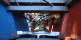 BOYS WILL BE BOYS. A boy plays with his younger brother in a dilapidated fishing boat docked near their house in Brgy. 76-A Bucana, Davao City while their mother is busy doing her laundry on Monday. LEAN DAVAL JR.