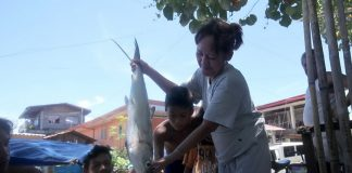 FISH CATCH. Residents of a coastal community in Brgy. 76-C Bucana, Davao City examine a huge fish caught by fishermen in Davao Gulf on Monday. LEAN DAVAL JR.