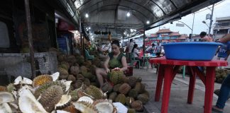 SEASON TREAT. A trader opens dozens of Durian fruit which will be processed into Durian jam, a favorite sandwich spread and dessert of Dabawenyos, at Magsaysay fruit stand in Davao City on Tuesday. LEAN DAVAL JR.