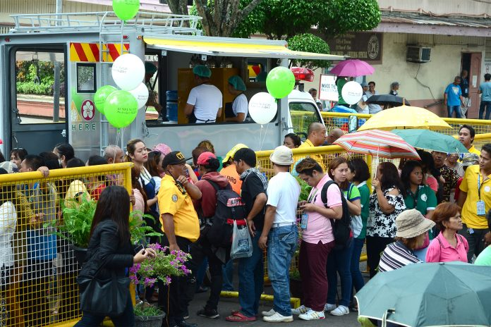 INSTANT HIT.Residents and government employees form a long queue in front of a mobile kitchen called 'Kusinang Bayan', a project of the city government of Davao that will serve quick hot meals to people affected by calamities, during its launching on Monday. LEAN DAVAL JR.