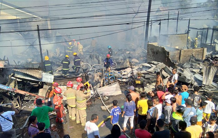 UP IN SMOKE. Personnel of Central 911's Urban Search and Rescue team clear the gutted houses after a fire in Muslim Village, Times Beach, Matina Aplaya on Thursday. ARMANDO B. FENEQUITO JR.