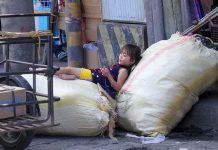 SOFT AS A BED. A daughter of a trader along Monteverde Street in Davao City makes the sacks containing ukay-ukay products her resting place on Tuesday afternoon. Lean Daval Jr.