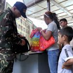 MAKING SURE. A boy looks on while a Task Force Davao personnel inspects his mother's belongings at the entrance of the Davao City Overland Transport Terminal (DCOTT) on Tuesday. Authorities implemented stricter security measures after government troops killed Abu Sayyaf leader Isnilon Hapilon and Omar Maute of the Maute group on Monday. Lean Daval Jr.