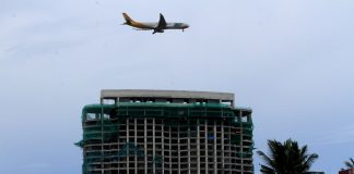 SMOOTH LANDING. An aircraft flies over the high-rise residential-commercial project of Aeon Towers along J.P. Laurel Avenue in Davao City on Saturday. Aircrafts can now land from the south side of the Davao City International Airport after Aeon Towers complied to remove a boom crane atop its building last month due to the Civil Aviation Authority of the Philippines complain that it has been causing disruption to air traffic. LEAN DAVAL JR.