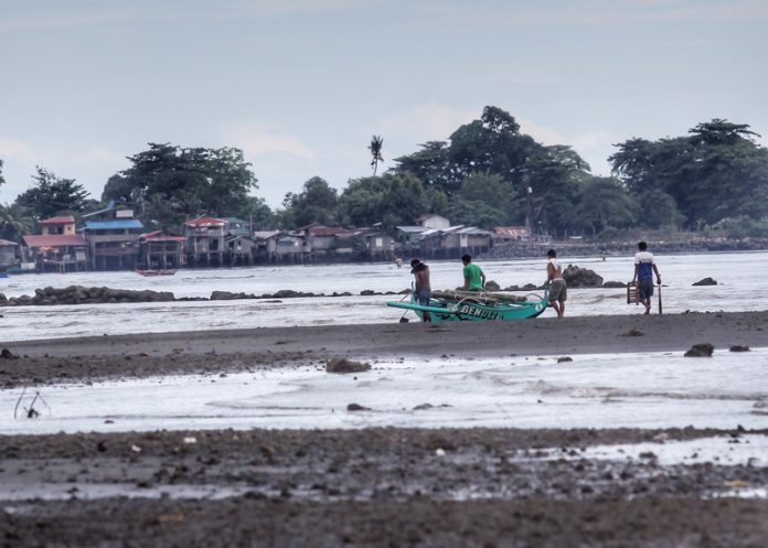 THE DAY'S CATCH. Fishermen carry their fishing boat towards a coastal community in Matina Aplaya on Wednesday after a day out in the Davao Gulf. Prices of sea produce are slightly up in Davao City due to a low pressure area (LPA) affecting some parts of Mindanao. LEAN DAVAL JR.