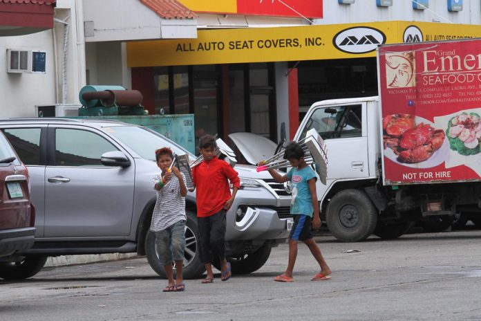 BREADWINNERS. Instead of going to school, these young hawkers roam around the establishments inside Victoria Plaza compound to peddle metal dustpans on Thursday morning. LEAN DAVAL JR.