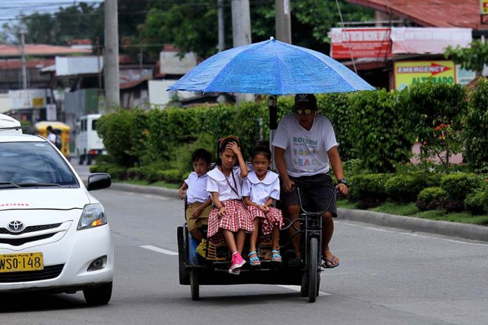 EVER RELIABLE. A man maneuvers his trisikad which is overloaded with young students along R. Castillo Street in Davao City on Thursday. LEAN DAVAL JR.