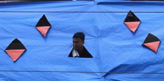 IN THE INTERIM. A worker peeks through a triangular shaped hole of a tarpaulin to watch pedestrians from the sixth floor of a building which is undergoing rehabilitation along Damaso Suazo corner R. Magsaysay Avenue in Davao City on Wednesday. LEAN DAVAL JR.