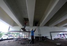 SPRUCING UP. Workers conduct a repainting work of Agdao flyover as part of the city's rehabilitation and maintenance on Tuesday. LEAN DAVAL JR.