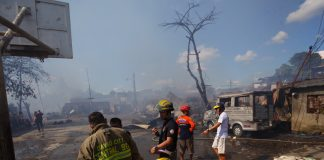 Members of Central 911 firefighting team take a rest while assessing the damage of the fire that razed a residential area in Brgy. Pag-asa in Davao Cityon Tuesday. LEAN DAVAL JR