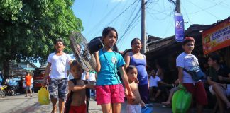 DISPLACED. A young resident, together with her brothers, carries an electric fan belonging to her family as they evacuate to the nearby Bankerohan Public Market after a huge fire razed their home in Brgy. Pag-asa, Bankerohan, Davao City on Tuesday afternoon. LEAN DAVAL JR