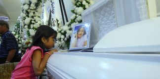 FIRE VICTIM. August watches her aunt Rhenzi Nova Muyco as she sits beside her coffin at Cosmopolitan Funeral Homes along Camus Street in Davao City on Wednesday night. Muyco is among the fatalities during Saturday's NCCC fire. LEAN DAVAL JR.