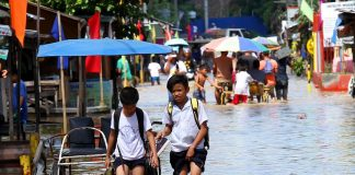 BOYS WILL BE BOYS. Two elementary students wade through flood water along Zunio Street in Brgy. Ubalde, Davao City as they take a break from their classes on Wednesday morning. The drainage system in the area overflowed after a compound where a hospital is being constructed released large volume of water brought by Tuesday night's heavy downpour. LEAN DAVAL JR.