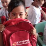 A kindergartener smiles behind his Phoenix Foundation backpack in a program where Phoenix employees spent time with the students and had games, food and performances.