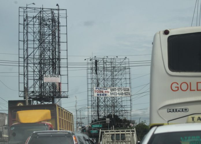 SUNSET BUSINESS? Photo shows empty metal structures for billboard advertisement tower over Quimpo Blvd. in Davao City on Monday. The outdoor advertisement is in a downward spiral as it is one of the affected industries after customers shifted to social media advertising. LEAN DAVAL JR .