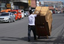 HEAVY LOAD. A porter struggles to maneuver a cart full of merchandise which he will deliver to customers along R. Magsaysay Avenue in Davao City on Monday. LEAN DAVAL JR .