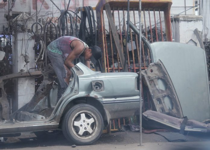 MACHINE SHOP SCENE. A machine shop worker dismantles a car which is undergoing a major repair at a makeshift shop along McArthur Highway in Davao City on Monday. LEAN DAVAL JR .