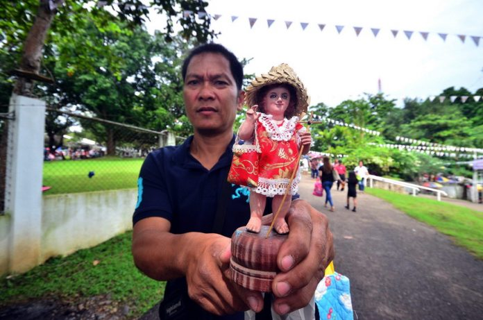 STO. NINO IMAGE. A devotee shows his miniature Sto. Nino image after it was blessed during the Golden Jubilee of the Shrine of the Holy Infant Jesus of Prague in Shrine Hills, Matina, Davao City on Monday. LEAN DAVAL JR.
