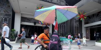 NEVER SAY DIE. A physically challenged vendor maneuvers his wheelchair towards an area where there is a large foot traffic to sell candles inside San Pedro Cathedral compound in Davao City on Wednesday. LEAN DAVAL JR.