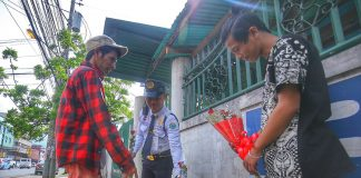 IN BUNCHES. A security guard chooses from a bunch of red roses that is being peddled by flower vendors to various establishments along R. Magsaysay Avenue in Davao City on Wednesday. LEAN DAVAL JR