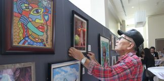 THE OTHER RBL. Veteran photojournalist Rene Lumawag makes a last minute adjustment of his art work, an acrylic on canvas entitled 'Still Life,' before the opening of an art exhibit of 25 artists from the Davao Artist group at the lobby of Park Inn by Radisson Davao on Tuesday. The art exhibit is for the benefit of Badjao children from the rainbow community in Matina Aplaya. LEAN DAVAL JR