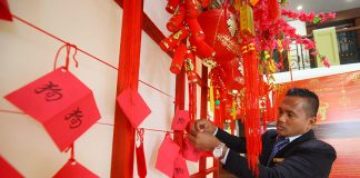 ALL IN ORDER. Jojo Ramos of the royal service team of The Royal Mandaya Hotel fixes the wish lists from the hotel guests hung on a wishing wall in time for the celebration of the Chinese New Yearon Thursday. LEAN DAVAL JR