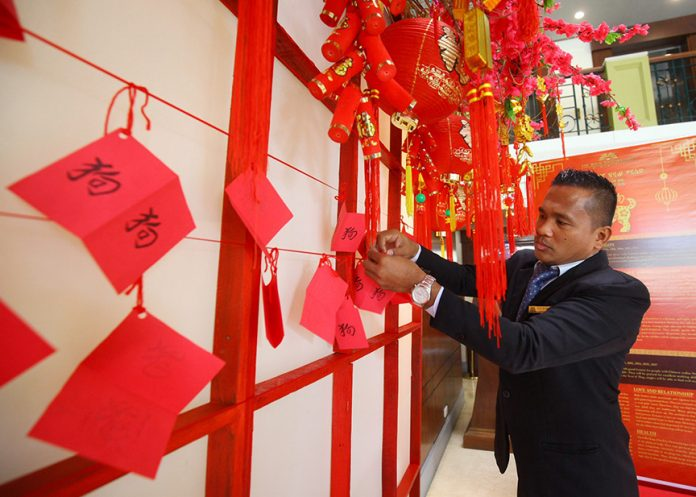 ALL IN ORDER. Jojo Ramos of the royal service team of The Royal Mandaya Hotel fixes the wish lists from the hotel guests hung on a wishing wall in time for the celebration of the Chinese New Year on Thursday. LEAN DAVAL JR