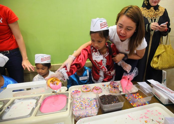 SAYING IT WITH DONUTS. A Krispy Kreme staff member helps a Tausug girl create her own original art through doughnuts as the company hosted its iconic Doughnut Tour and Create-Your-Own-Doughnut activity with 10 indigenous kids from the different tribes of Davao at its branch at SM City Davao on Wednesday. The company also launched its Araw ng Davao treat and other summer season promotions. LEAN DAVAL JR