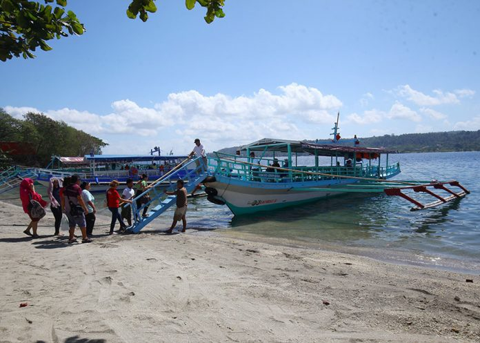 UNEASY ON LOCKDOWN. Beach goers form a queue as they wait to board an Island Garden City of Samal (IGaCoS)-bound motorized boat at a jetty of one of the resorts in the island in Km. 9 Sasa, Davao City on Monday. Resorts owners in Samal are concern about the 12-hour road lockdown's effects on their businesses on March 25 to give way to the IronMan 70.3 event. LEAN DAVAL JR