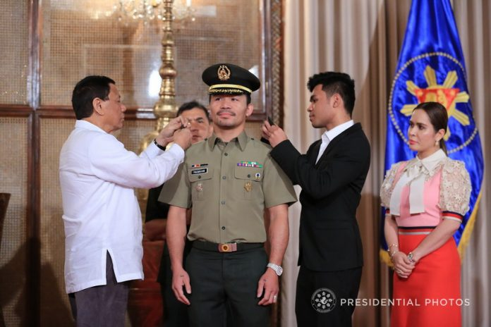 IN THE SERVICE. President Rodrigo Duterte pins the rank insignia on newly-promoted Philippine Army reserve Colonel Senator Emmanuel Pacquiao during a ceremony at the Malacañan Palace on Tuesday. PRESIDENTIAL PHOTO