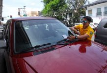 "REMINDER. An enforcer from the City Transport and Traffic Management Office (CTTMO) places fliers printed with ""No Parking"" warning on the windshield of a vehicle parked along Pelayo Street in Davao City on Thursday, a day before the culmination of the 81st Araw ng Davao. LEAN DAVAL JR"