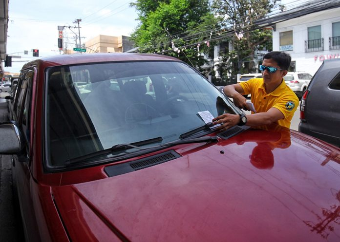 """REMINDER. An enforcer from the City Transport and Traffic Management Office (CTTMO) places fliers printed with """"No Parking"""" warning on the windshield of a vehicle parked along Pelayo Street in Davao City on Thursday, a day before the culmination of the 81st Araw ng Davao. LEAN DAVAL JR"""