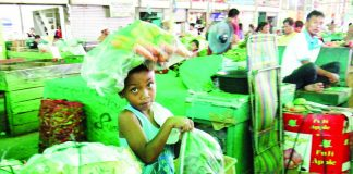 A young boy carries plastic bags full of vegetables as he works as a porter instead of spending his summer break playing with his peers at the 'bagsakan area' of Bankerohan Public Market on Wednesday. LEAN DAVAL JR