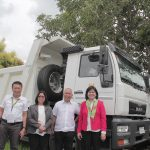 DAR Officials, led by Undersecretary Emily Padilla, pose for a photo in front of one of the hauling trucks. Also in photo: Regional Director Leomides Villareal, Asst. Reg. Dir. Naylinda Narisma,