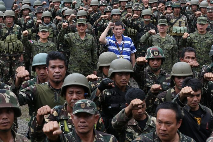 President Rodrigo Road Duterte poses with members of the military during his visit at the 103rd Brigade in Lumbayanague town, Lanao del Sur on November 30,2016. TOTO LOZANO/Presidential Photo