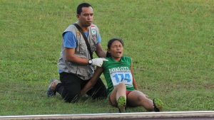 INJURED. A trackster from Philippines-Mindanao is attended to by a member of the medical team during the 9th BIMP EAGA Games in Samarina, Indonesia. CIO