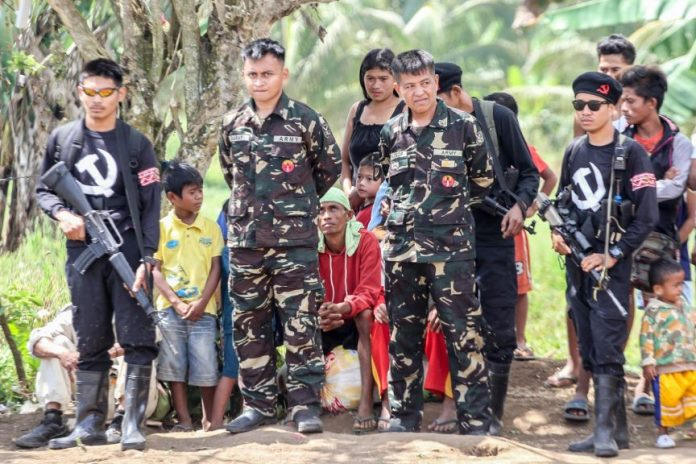 "Members of the New People's Army guard their ""prisoners of war,"" Pfc Samuel Garay (2nd from L) and Sgt Solaiman Calocop (3rd from L) of the 39th Infantry Battalion before the two soldiers were released to government officials and peace advocates in the hinterlands of Matanao, Davao del Sur on April 19, 2017. Garay and Calocop were captured by the NPA on February 2, 2017 in Columbio, Sultan Kudarat while they were on their way to Makilala, North Cotabato. MindaNews photo by Manman Dejeto"