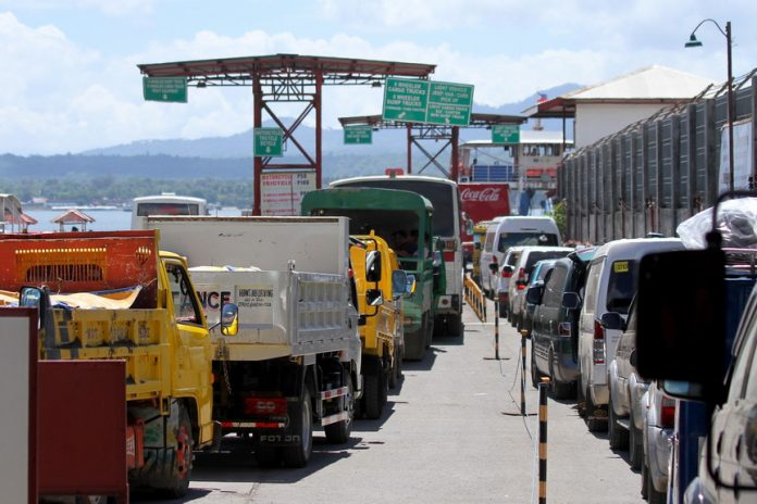 PILE-UP. Vehicles owned by beach-goers waiting for their turn to board a Roll-on/Roll-off vessel to the Island Garden City of Samal (IGaCoS) form a queue stretching out to two kilometers long in Sasa, Davao City on Saturday. Beach lovers flocked to IGaCoS for summer break outing and Holy Week celebration. LEAN DAVAL JR.
