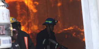 AFTERMATH. A firefighter from Filipino Chinese Firefighters Foundation of Davao, Inc. attempts to extinguish the fire at Lapanday Box Plant in Mandug, Davao City on Saturday morning. New People's Army rebels from the 1st Pulang Bagani Battalion launched simultaneous attacks and burned the plants of Lorenzo-owned companies as punitive action for the alleged numerous crimes against agricultural workers, peasants and Lumads. LEAN DAVAL JR.