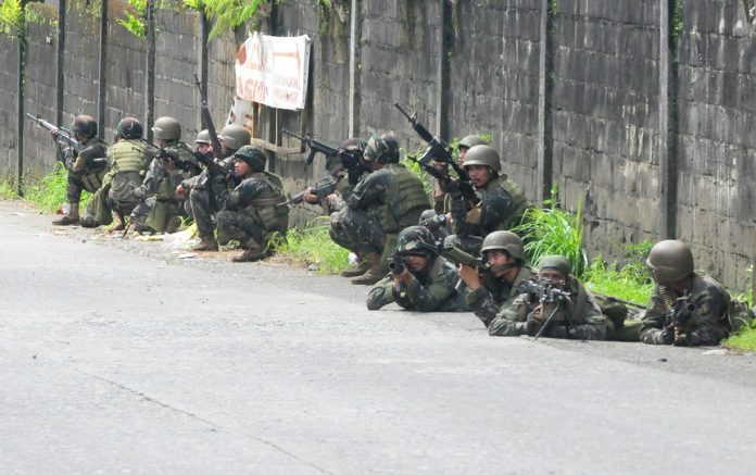 Army Scout Rangers duck for cover beside a wall after Maute gunmen fired shots at them in Marawi City on May 27, 2017. MindaNews photo by Froilan Gallardo