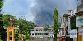 "A thick smoke billows from the back of buildings after an air strike by Philippine Air Force jets in Marawi City noon on Wednesday (14 June 2017). On the left is Marawi's ""Kilometer Zero"" marker, which is a stone's throw away from the Amai Pakpak Medical Center. Most of Marawi City remains a ghost town after 24 days of heavy fighting between government soldiers and the Maute Group. MindaNews photo by Froilan Gallardo"